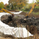Blunk-Team beim Entschlammen von Regenrückhaltebecken in Albersdorf mit Befüllung des Polders